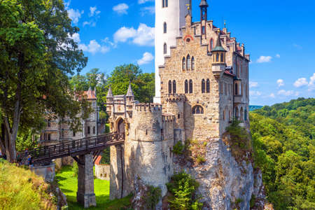 Lichtenstein Castle in summer, Germany. This amazing castle is a landmark of Baden-Wurttemberg. Scenic view of magic Lichtenstein Castle with bridge on a cliff. Mountain landscape of Swabian Alps.