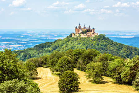 Landscape with Hohenzollern Castle, Germany. This fairytale castle is a famous landmark near Stuttgart. Scenic panorama of mount Burg Hohenzollern and fields. Scenery of Swabian Alps in summer.