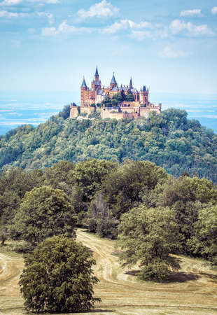 Castle Hohenzollern on top of wooded mountain, Baden-Wurttemberg, Germany. Famous Burg Hohenzollern is landmark in Swabia. Scenic view of fairy tale German castle like palace in summer. Editorial