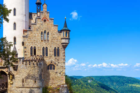Lichtenstein Castle on blue sky background, Germany. It is a famous landmark of Baden-Wurttemberg. Scenic view of magic castle on a cliff. Mountain landscape of Swabian Alps in summer.