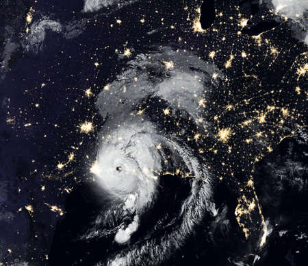Storm Laura over USA at night, tropical hurricane eye from space. Typhoon landfall and city lights of Earth on satellite photo. Weather and warning concept.