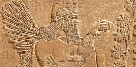 Assyrian wall relief of winged genius, old carving panel from Middle East. Remains of fine art of ancient Babylonian and Sumerian civilization in Mesopotamia. History and mythology of Iran and Iraq. Stock Photo