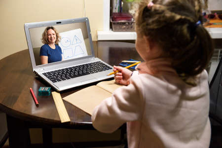 Online home education, tutor teaches preschool child during quarantine due to coronavirus. Kid learning with teacher by laptop. Concept of virtual distance lesson and elearning study technology.