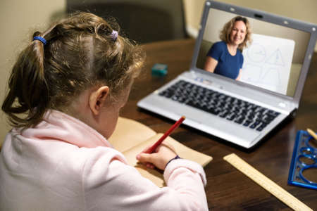 Kid virtual learning with teacher by laptop, little girl studies online in room, tutor teaches preschool child during quarantine. Concept of distance lesson, home education and elearning technology. 免版税图像