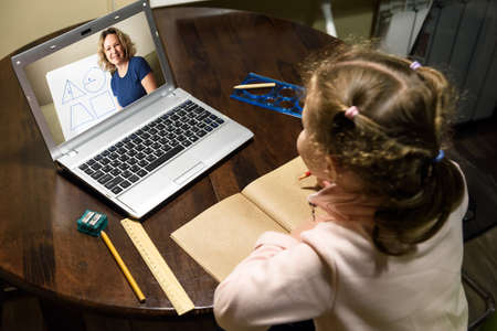 Kid virtual learning with teacher by laptop, tutor teaches preschool child during quarantine due to coronavirus. Concept of distance lesson, online home education and elearning study technology.