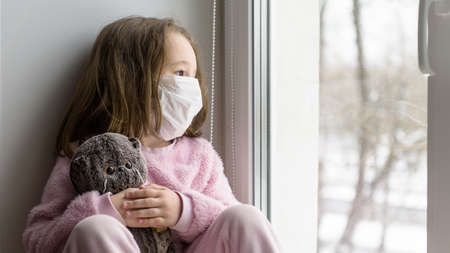 COVID-19 coronavirus concept, sad kid in medical mask looks out window. Pensive child sits on windowsill at home in autumn or winter. Little girl with toy during quarantine safe from corona virus.