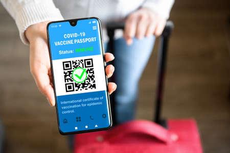 COVID-19 vaccination passport in mobile phone for travel, tourist holds smartphone with health certificate app, digital coronavirus pass. Concept of corona virus, immunity passport and tourism. Archivio Fotografico