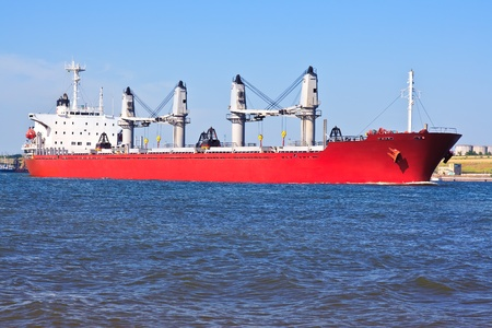 Red cargo ship in the harbour. photo