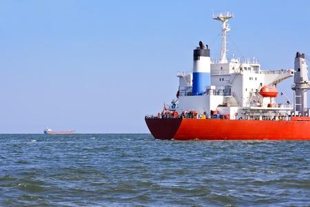 convoy: Convoy. A feed of the red cargo ship. Stock Photo