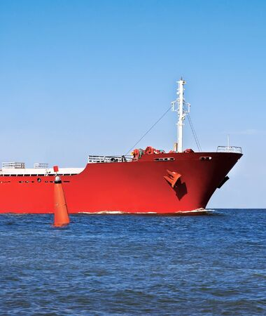 ship bow: Bow of the red cargo ship in the ocean and a red buoy.