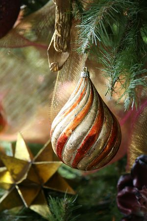 Large Christmas Bulb with Swirls of Glitter Hanging on Tree Stock Photo