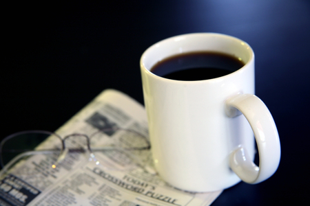 Cup of Coffee and Newspaper with Reading Glasses