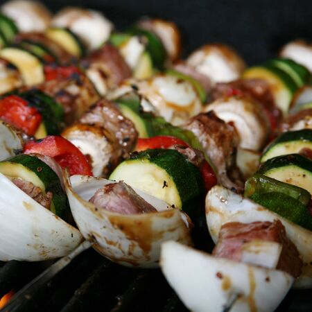 shish kabobs on grill with sirlion, zucchini, red bellpeppers, green peppers, oinions, and mushrooms Stock Photo