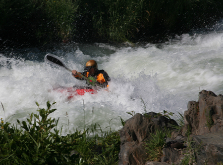 A kayaker battling strong rapids on the Rogue River in Oregon Stock Photo