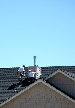 Construction Workers on Roof Working on Siding Chimney Stock Photo