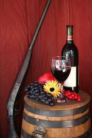 antique rifle: Wine Glass and Bottle with Grapes on Oak Barrel