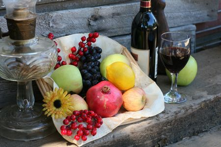 wine country: Harvest Basket filled with Fruit, Wine Bottle and Glass Stock Photo