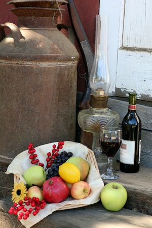 hurricane lamp: Harvest Basket filled with Fruit, Wine Bottle and Glass Stock Photo