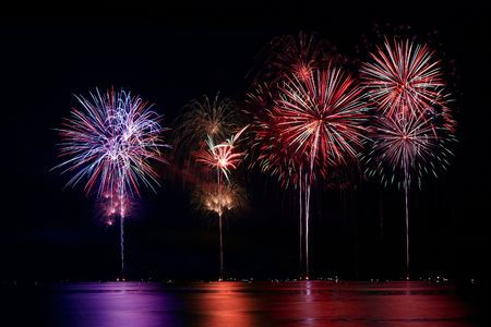 finale: Colorful Firework Show Finale with Multiple Bursts Reflecting in Water at Lake Stock Photo