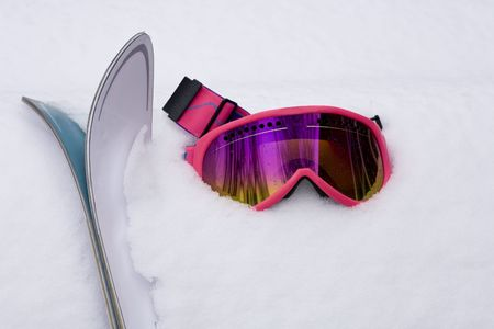 Hot Pink Ski Goggles and Skis in Snow Stock Photo