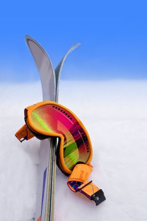 protective goggles: Neon Orange Ski Goggles in Snow with Skis Stock Photo