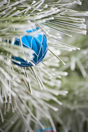 frost covered: Blue Christmas Ornament hanging on a frost covered pine tree outdoors with copy space