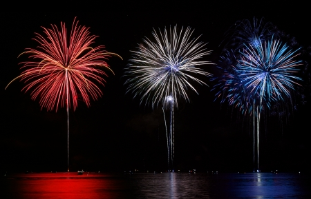 new year's day: Red, White & Blue Fireworks reflecting in lake Stock Photo
