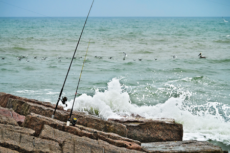 Fishing rods and reels on jetty with waves