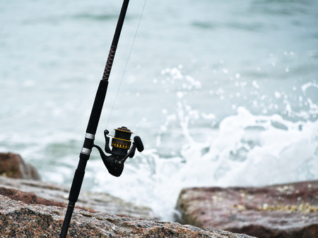 Fishing rod and reel on jetty with waves