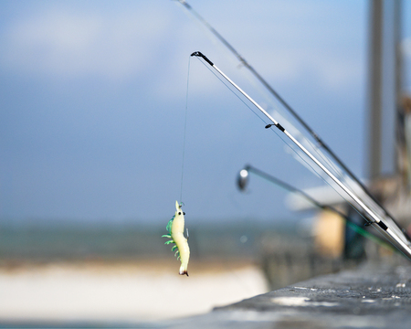 Fishing lure on pier with fishing poles and beach in background in background