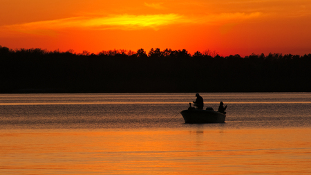 Silhouette of father and son fishing on Lake Irving at sunset in Bemidji, Minnesota. Stock Photo