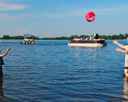 Pontoon boats with families having fun at sandbar on Lake Irving in Bemidji Minnesota. Throwing a beachball. Stockfoto