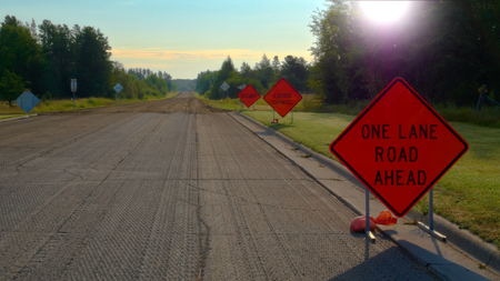 Orange Warning Road Signs on highway at construction site on sunny morning