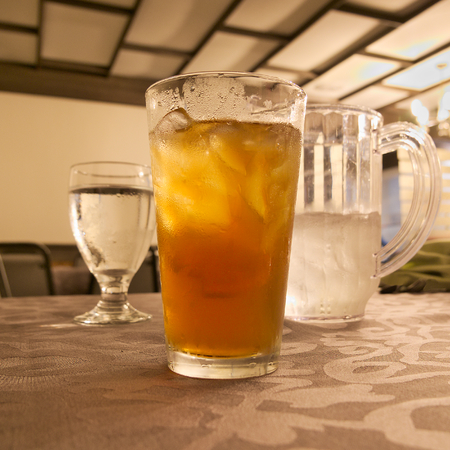 glass of cold iced tea with ice and goblet and pitcher of water on restaurant table