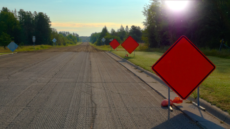Orange Warning Road Signs on highway at construction site on sunny morning. ADD YOUR TEXT Stock Photo