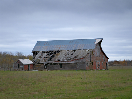 Drab Abandoned Dilapidated Farm Barn and Shed with clouds in northern Minnesota Stock fotó