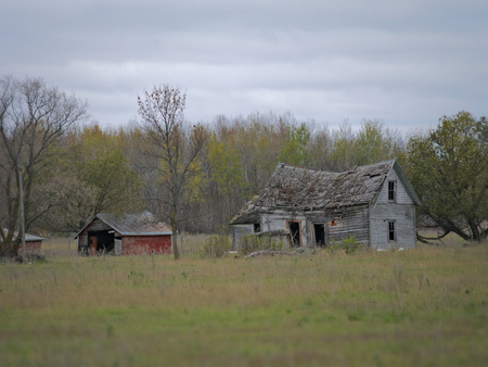 Drab Abandoned Dilapidated Farm House and Shed with clouds in northern Minnesota