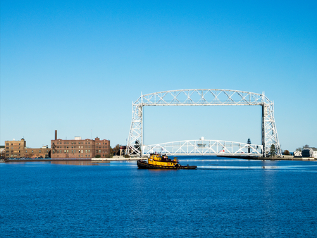 Yellow Tug Boat sails near Duluth Minnesota aerial lift bridge in late afternoon on sunny day