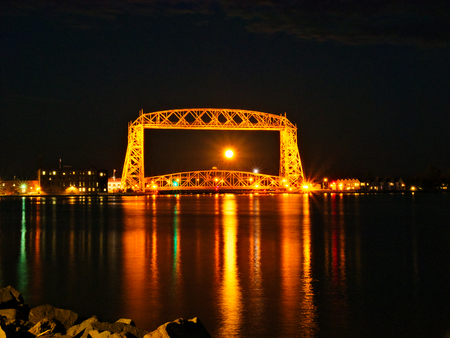 Full moon is seen through the iconic Duluth Minnesota aerial lift bridge with reflections on calm harbor waters