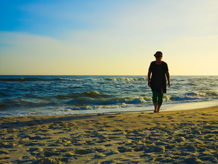 Silhouette of retired senior woman walking barefoot on Gulf of Mexicao beach sand in evening at Orange Beach, Alabama.