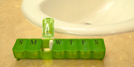 seven day green pill box with pills sits on countertop near sink.