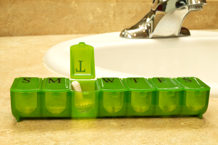 seven day green pill box with pills sits on countertop near sink with faucet