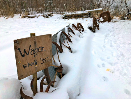 Antique wagon wheels with for sale sign are lined up in the snow in northern Minnesota in December. Stok Fotoğraf