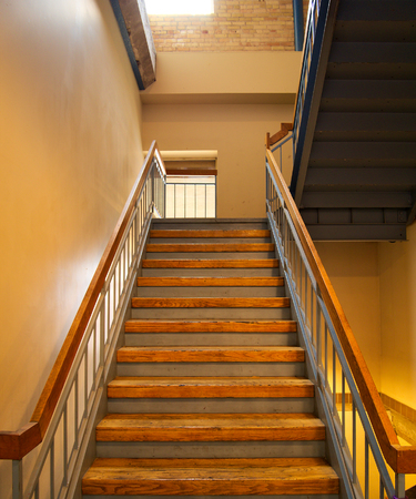 Metal and wooden Stair with beige wall, railings and shadows. Stairway, staircase, stairwell.