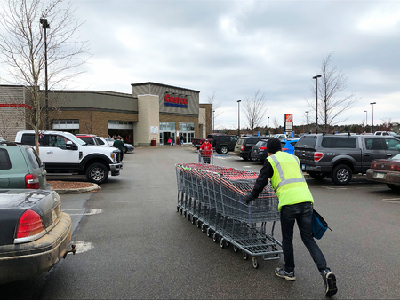 BAXTER, MN - NOVEMBER 23, 2018: Costco Cart Attendant pushes carts back to store from parking lot on cloudy day Editöryel