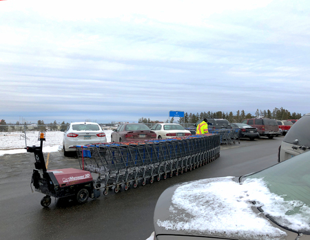BEMIDJI, MN - NOVEMBER 21, 2018: Walmart Cart Attendant returns carts back to store from parking lot on cloudy day