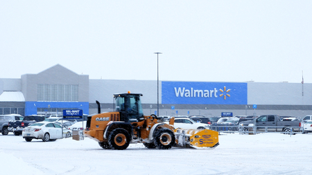 BEMIDJI, MN - DEC 27, 2018: Snow removal machine clearing Walmart parking lot during storm. Editöryel