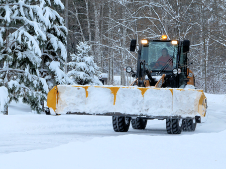 BEMIDJI, MN - DEC 28, 2018: Snow removal machine driving on street after storm. Evergreen tree branches are snow covered.