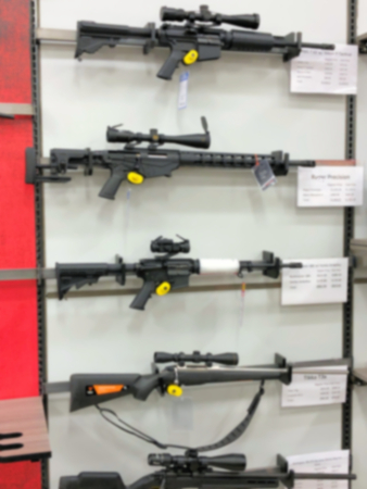 Blurred photo of gun rifle display for sale in sporting goods store shop. Stok Fotoğraf