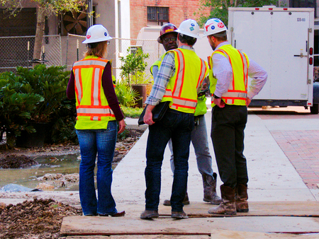 San Antonio, TX - March 6, 2017: Construction managers in orange work vests and helmets discuss documentation regarding building project.